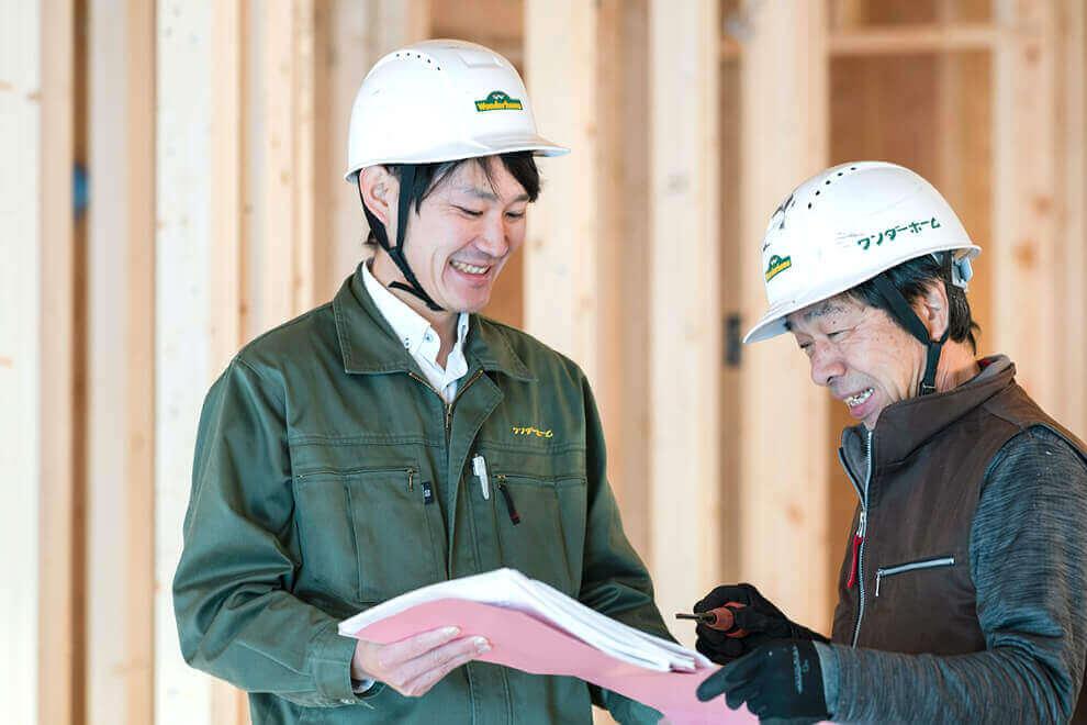 建築現場で相談しているスタッフの写真