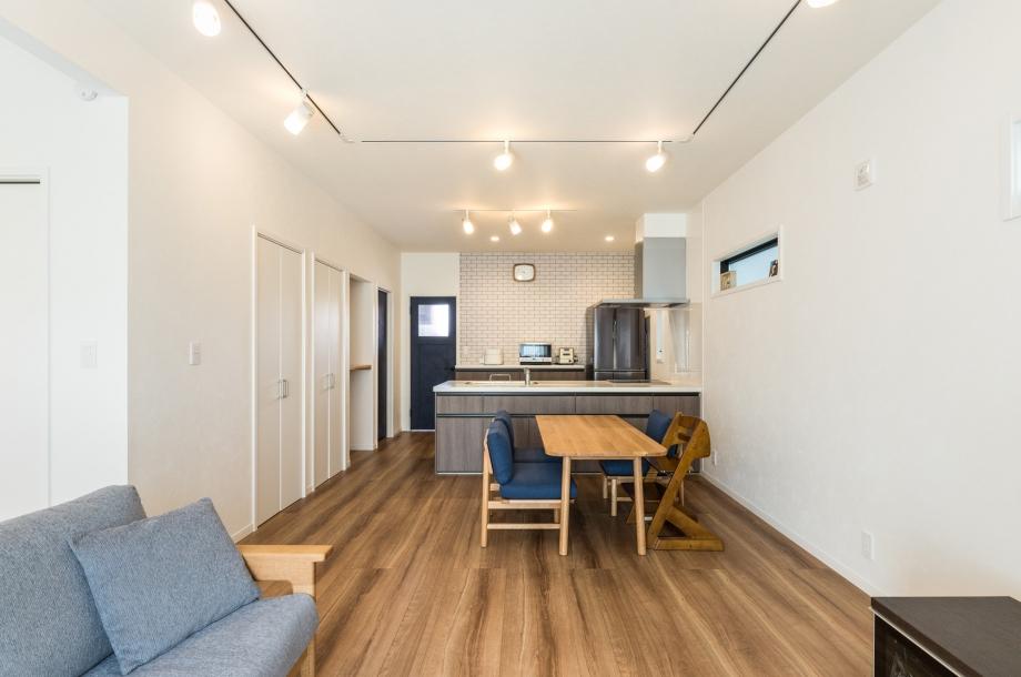 ナチュラルで淡い色合いが特徴のLDK。将来家具の配置を変えても対応できるように天井はレール式の照明になっています。