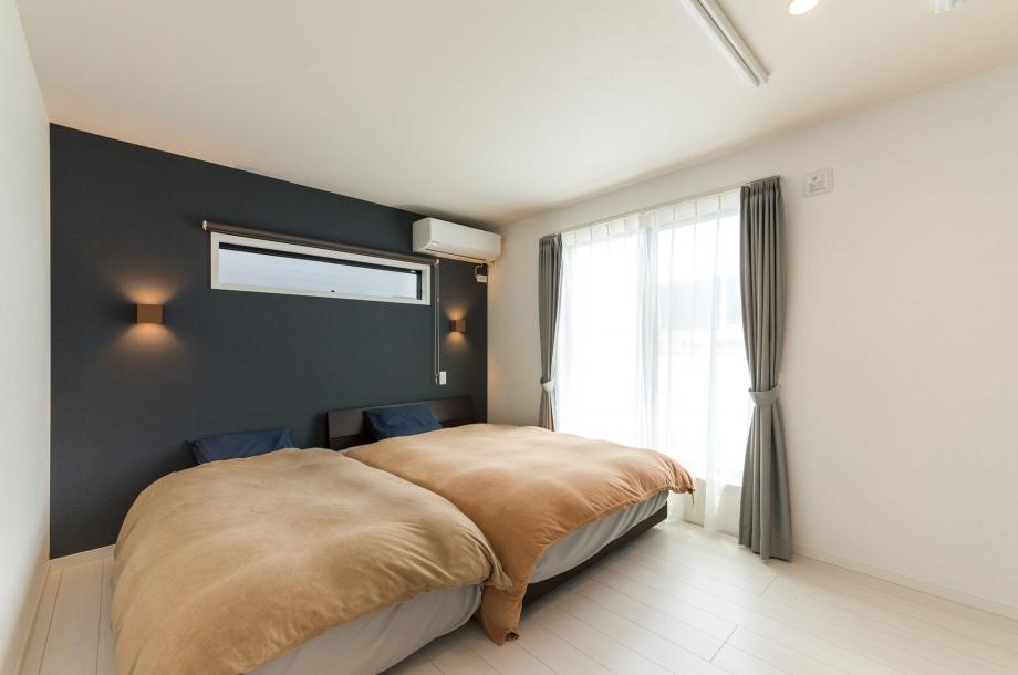 ネイビーのアクセントクロスが落ち着いた雰囲気の寝室。照明やコンセントなども使いやすい位置にあり、リラックスして使えそうです。