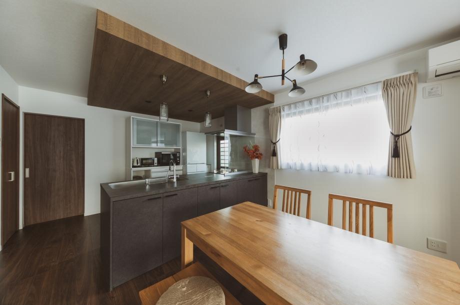 天井をあえて少し下げて木目調のクロスを貼ることでキッチンに特別感を出しています。