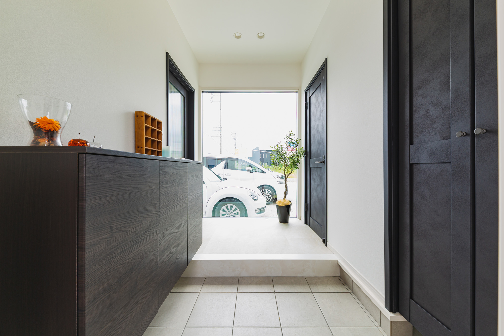 家の顔でもある玄関は大きな窓をつけることで、より広く開放感のある空間に仕上げています。